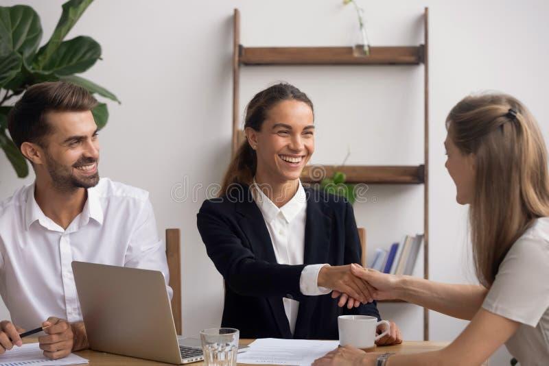 握手的微笑的HR代理祝贺有成功的采访的候选人 图库摄影