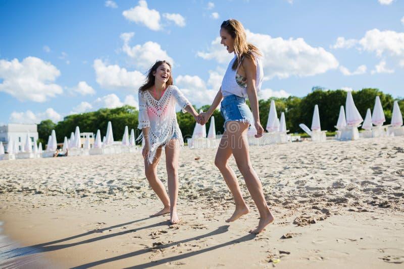 握手的愉快的俏丽的妇女走在海滩 库存照片
