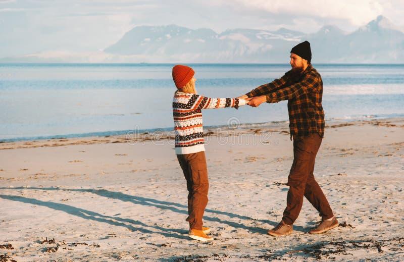 握手的愉快的夫妇走在海滩人和妇女年轻家庭 免版税图库摄影
