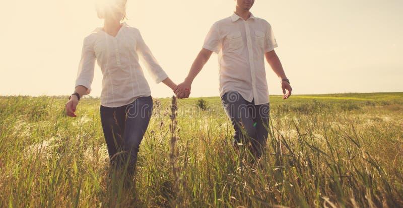 握手的愉快的夫妇走通过草甸 免版税库存照片