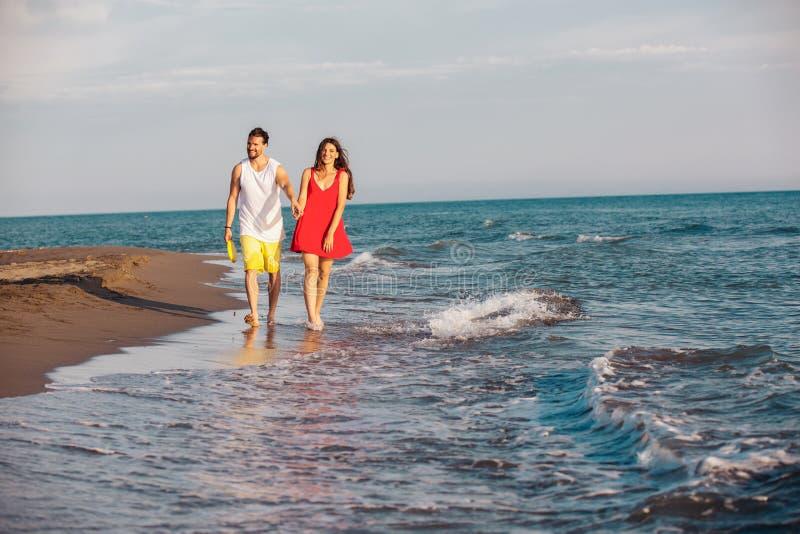握手的愉快的微笑的夫妇走在海滩 免版税库存图片