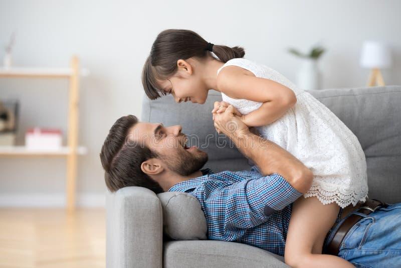 握手的愉快的爸爸和孩子女孩使用在沙发 免版税库存照片