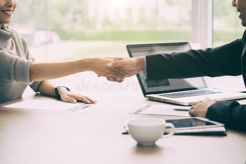 握手的成功的工作亚洲商人和女实业家在证券交易经纪人行情室,当结束会议时 库存图片