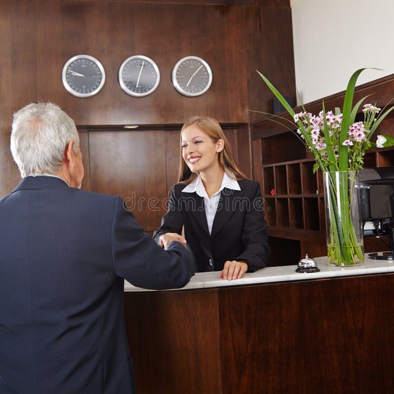 给握手的接待员资深客人 库存照片