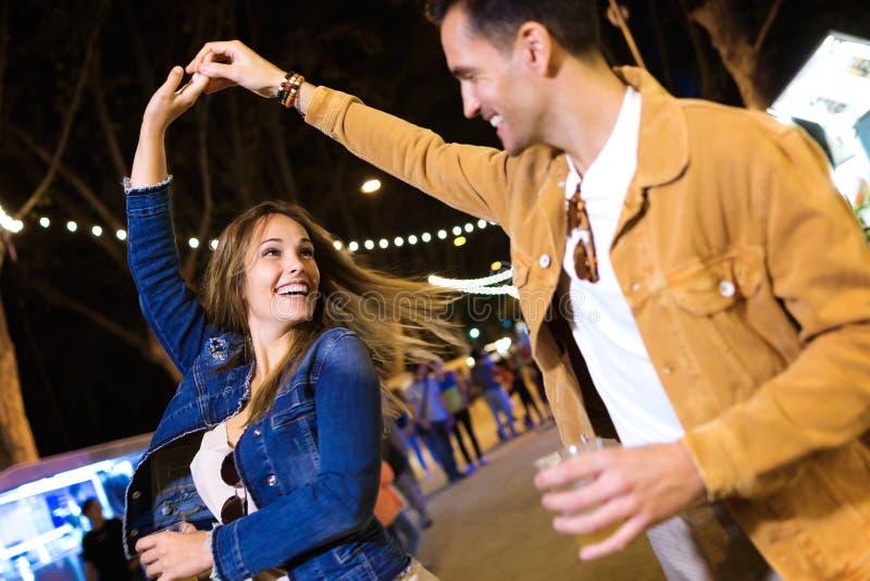 握手的无忧无虑的年轻夫妇跳舞在晚上吃在街道的市场 免版税库存照片