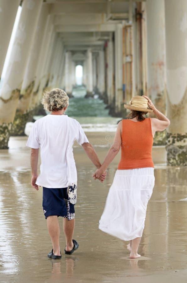 握手的浪漫成熟男人&妇女走在海滩 免版税库存照片