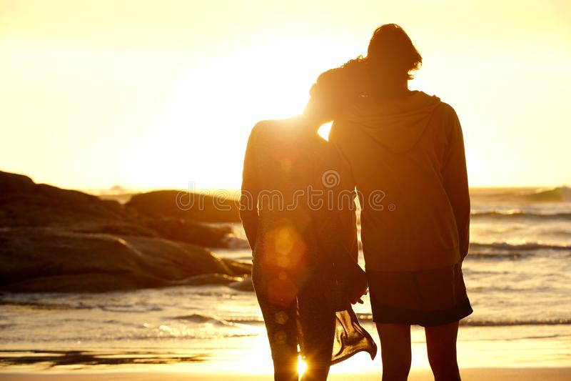 握手的爱恋的夫妇在观看日落的海滩 库存图片
