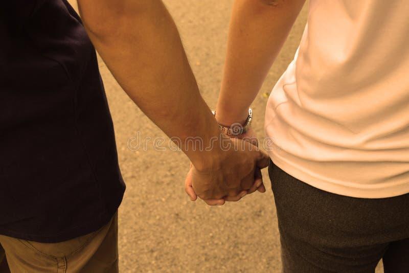 握手的爱恋的夫妇,当走时 免版税库存图片