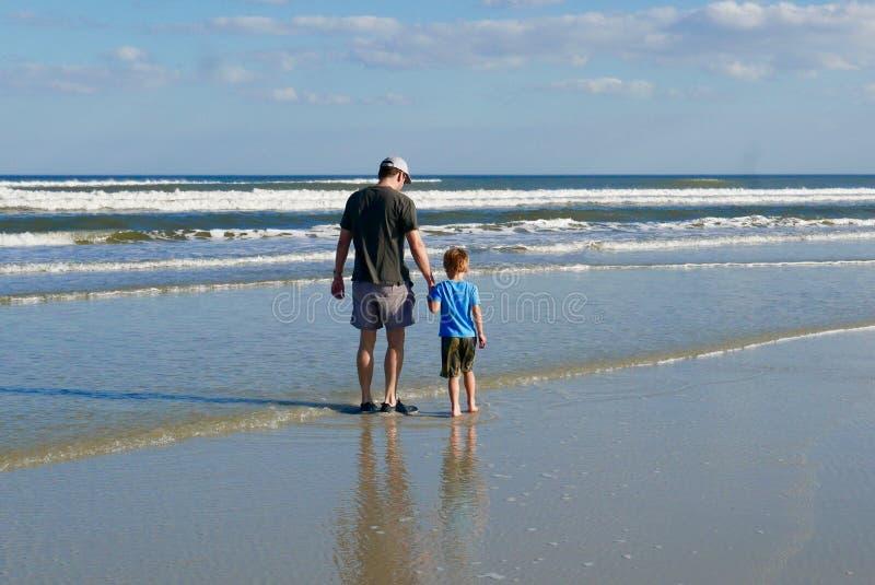 握手的父亲和儿子,当走在海滩时 库存照片