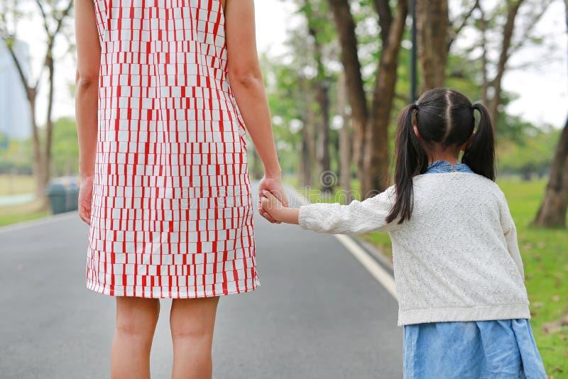 握手的特写镜头妈妈和女儿在室外自然庭院里 r 免版税库存图片
