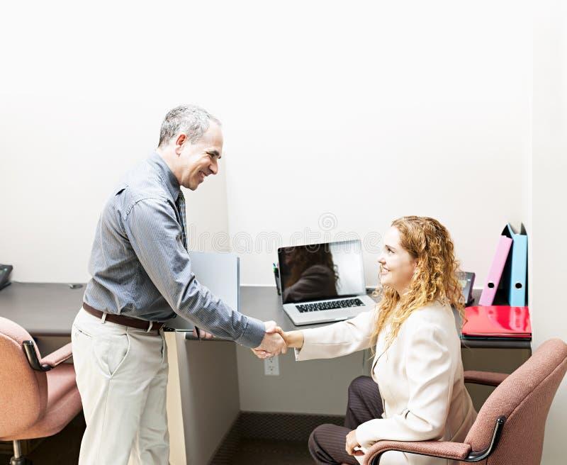 握手的男人和妇女在办公室 免版税库存照片