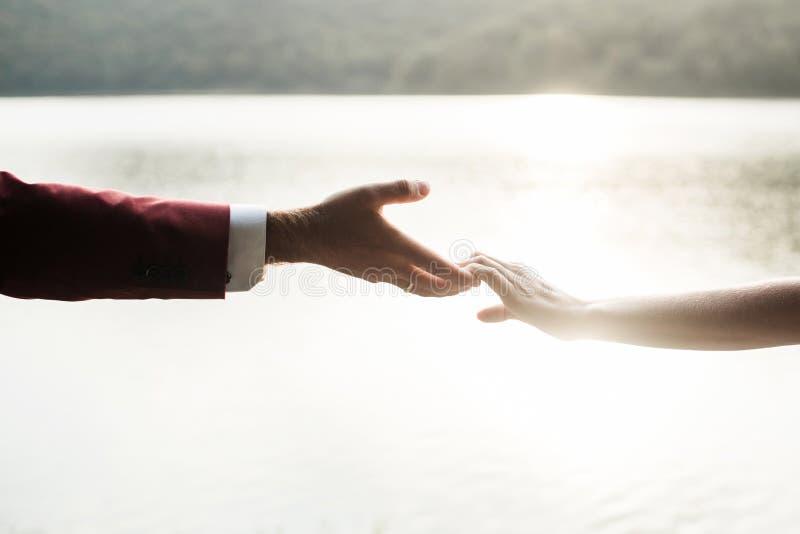 握手的男人和妇女在日落 免版税图库摄影