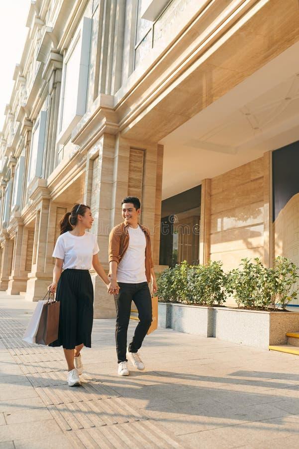 握手的美好的年轻不同的旅游夫妇走通过街道在城市 免版税库存照片