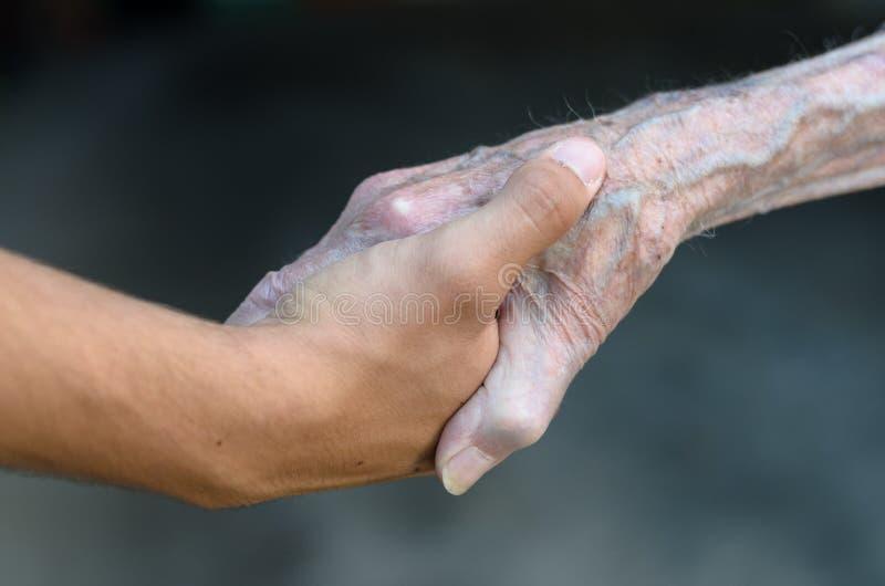 握手的老和年轻人 库存图片