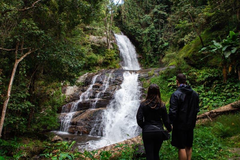 握手的背包徒步旅行者夫妇面对美丽的瀑布在清迈(;泰国 图库摄影
