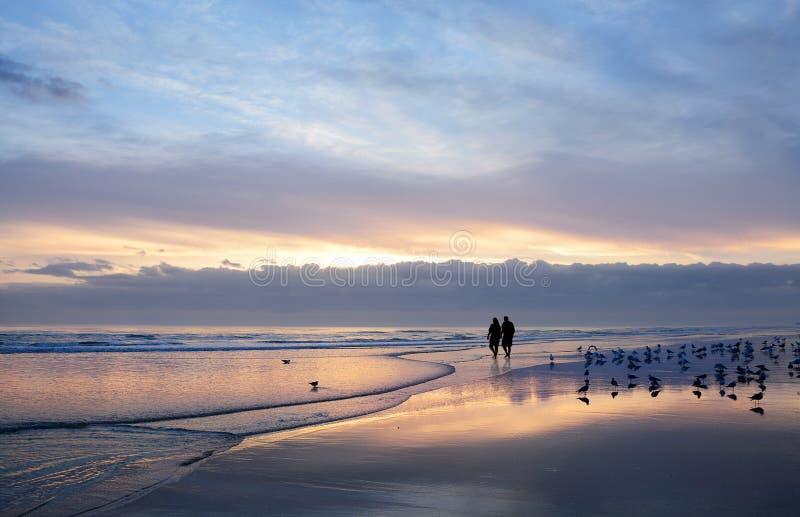 握手的资深夫妇享受在海滩的时间在日出 免版税库存图片