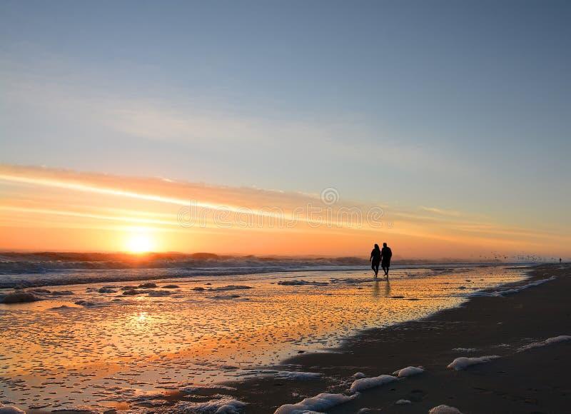 握手的资深夫妇走在享受日出的海滩 免版税图库摄影