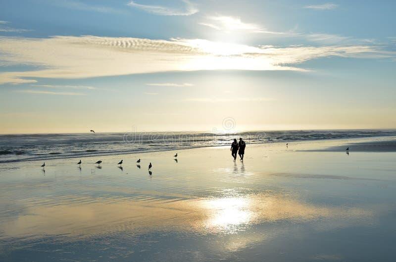 握手的资深夫妇走在享受日出的海滩 库存照片