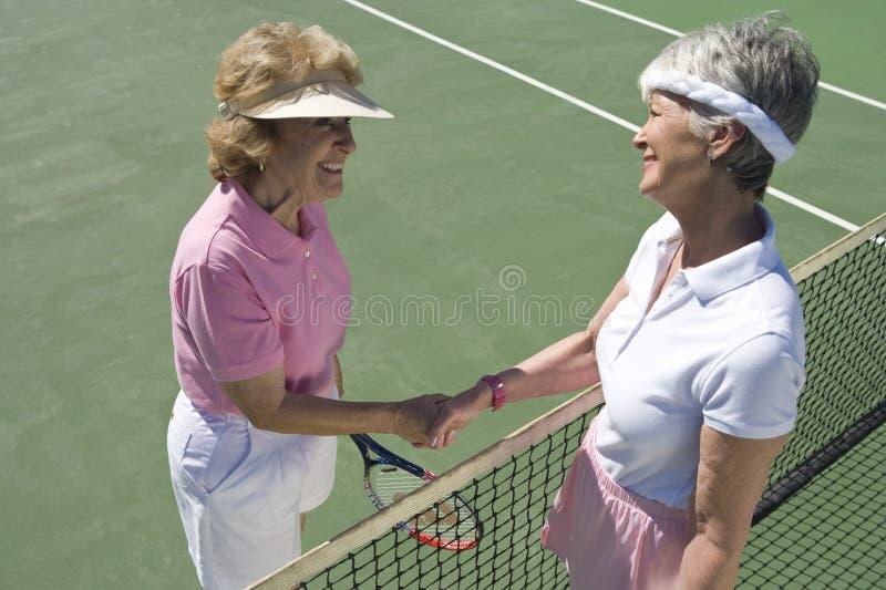 握手的资深女性网球员 库存照片
