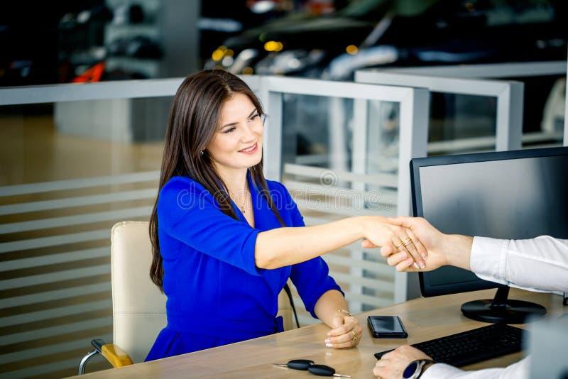 握手的销售主任和女性顾客祝贺在经销权陈列室 库存照片