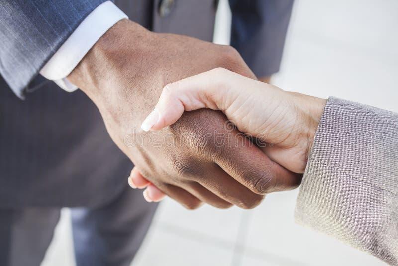 握手的非洲裔美国人的生意人&妇女 免版税库存照片