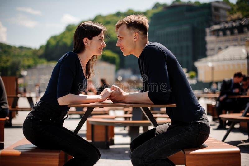 握手的年轻和有吸引力的夫妇亲吻在桌在餐馆 免版税图库摄影