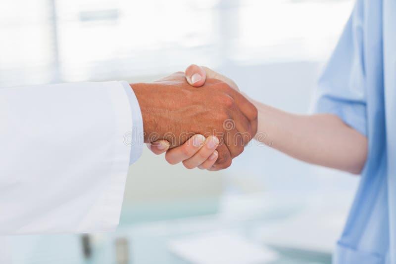握手的医生和护士的手 图库摄影