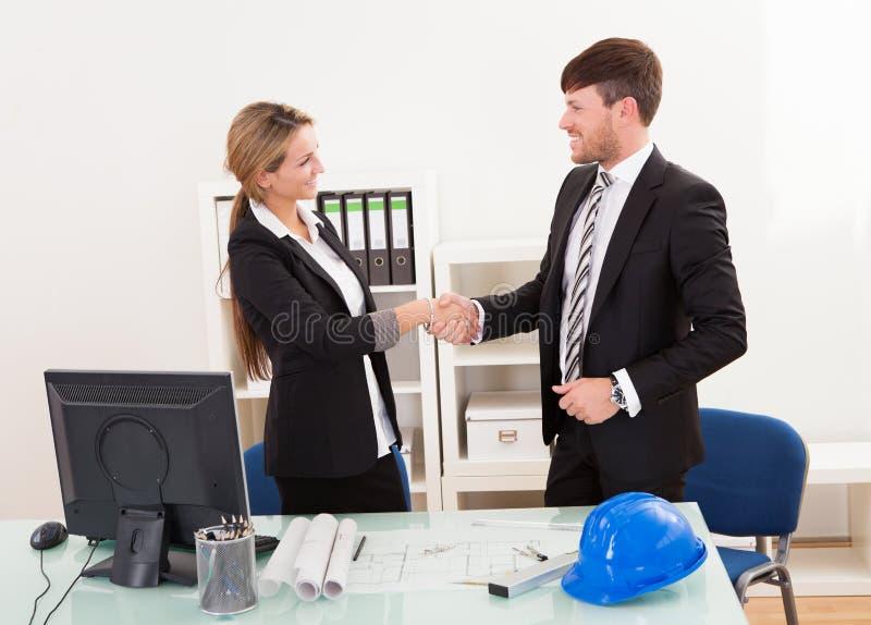 握手的建筑师在办公室 免版税库存图片