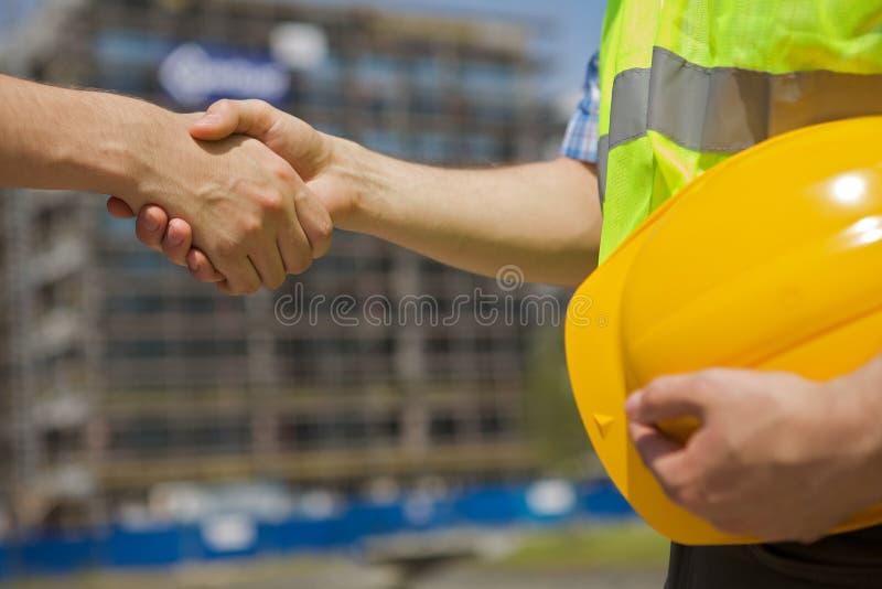 握手的建筑师在建造场所 免版税库存照片