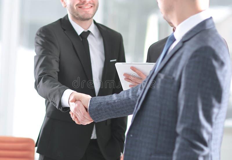 握手站立在银行办公室旁边的商务伙伴 免版税图库摄影