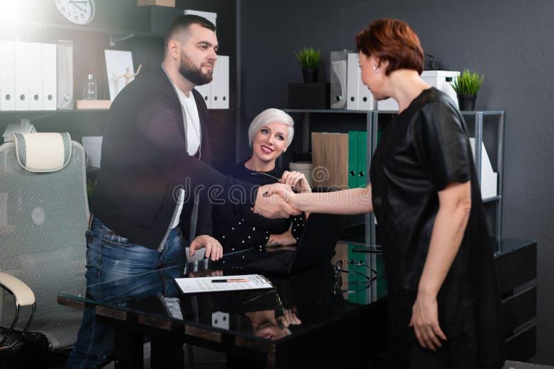 握手身分在现代办公室,见到你很高兴 免版税库存照片
