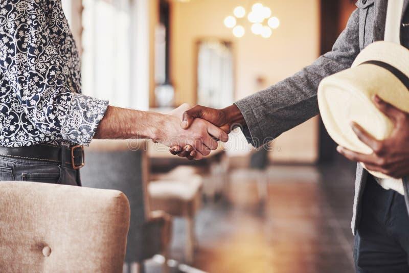 握手,满意的不同种族的偶然商人的黑白企业家束缚生意与 免版税库存照片