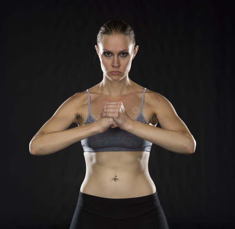 握拳头的强烈的运动妇女在演播室 免版税库存照片