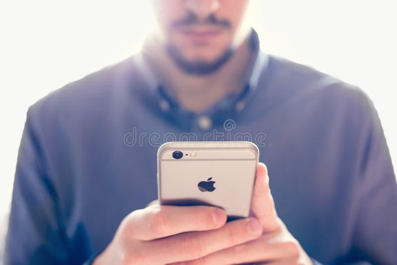 握新的苹果计算机iPhone 6s视网膜的商人 免版税库存照片