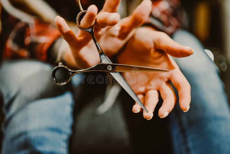 握有剪刀的女孩美发师手切开的头发特写镜头 库存图片