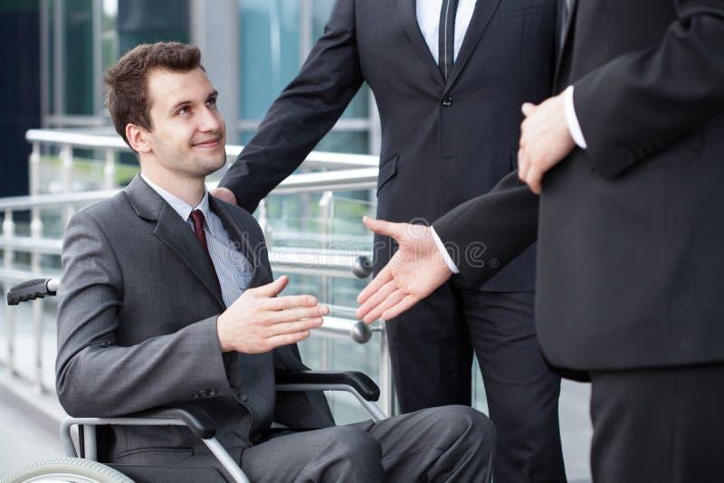 握有商务伙伴的残疾商人手 免版税库存照片