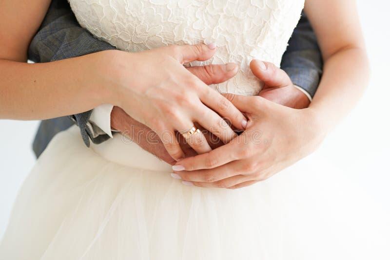 握有圆环的年轻已婚夫妇手在白色背景,仪式婚礼那天 免版税库存图片