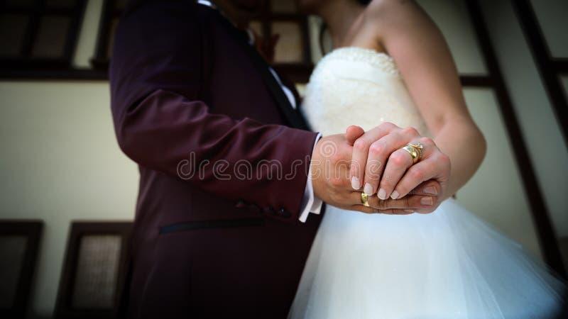 握有定婚戒指的新娘和新郎手在他们的手指接近看法婚礼射击概念 图库摄影