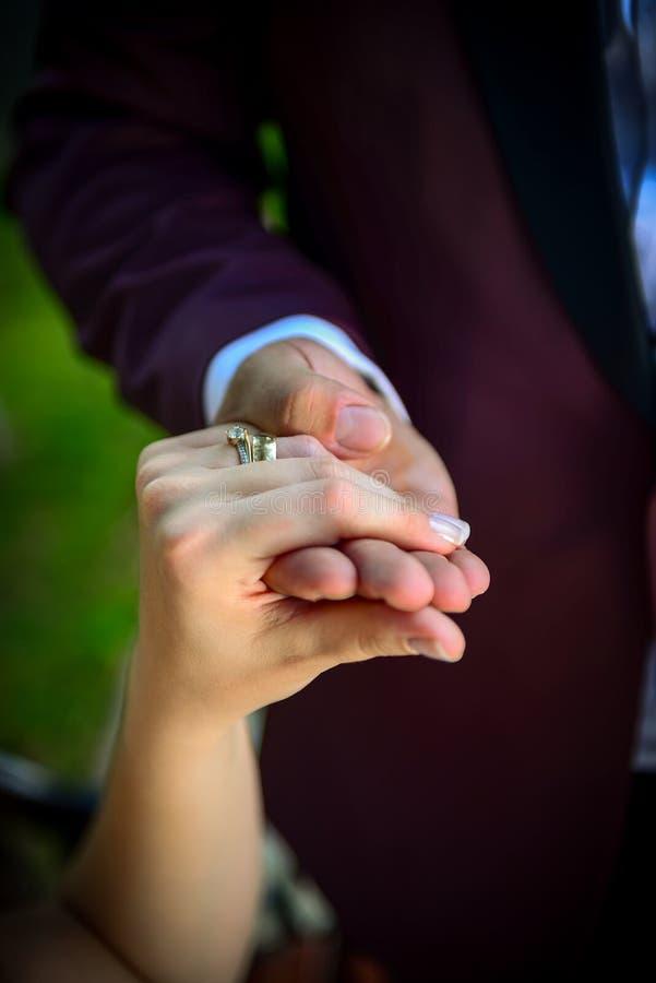 握有定婚戒指的新娘和新郎手在他们的手指接近看法婚礼射击概念 库存图片
