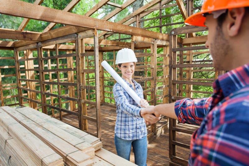 握有男性同事的愉快的建筑师手 免版税库存图片