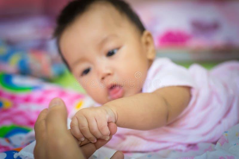 握母亲的手指的逗人喜爱的新出生的婴孩手 库存照片