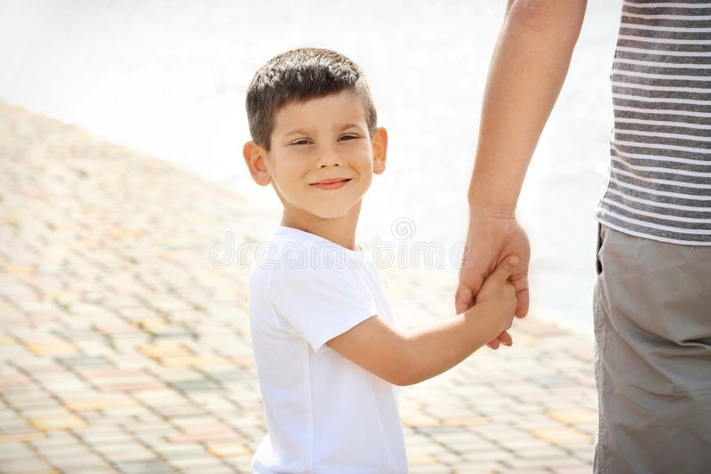 握父亲` s手的小男孩 免版税库存照片