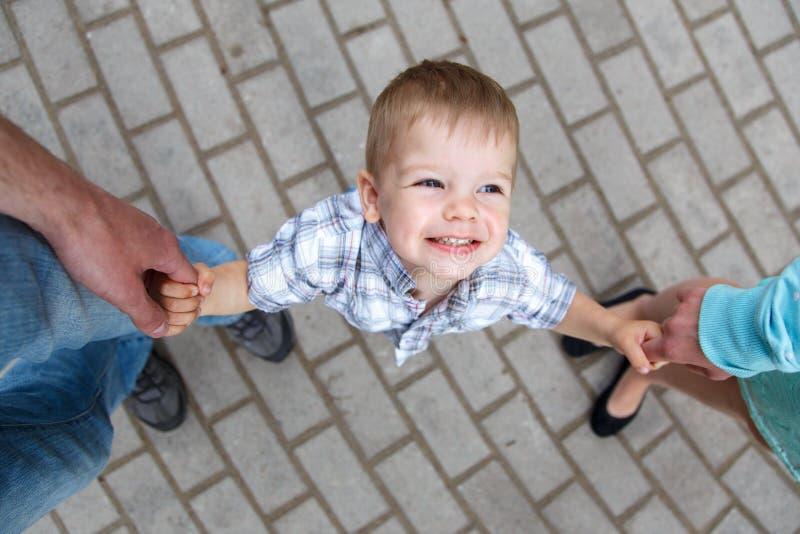 握父母的手指的愉快的小男孩 免版税库存照片