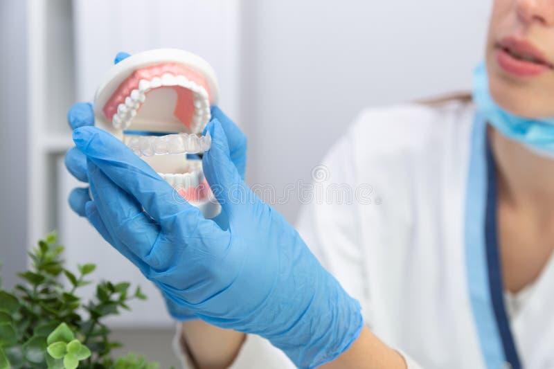握牙的女性牙医塑造和正牙学硅树脂教练员 无形的括号直线对准器 流动正牙学装置为 图库摄影