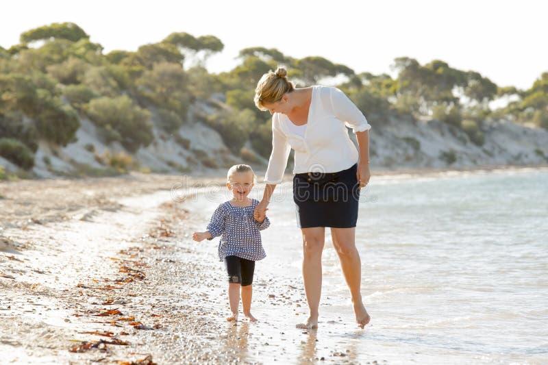 握甜白肤金发的矮小的女儿的手的愉快的母亲一起走在沙子在海滩海岸 图库摄影