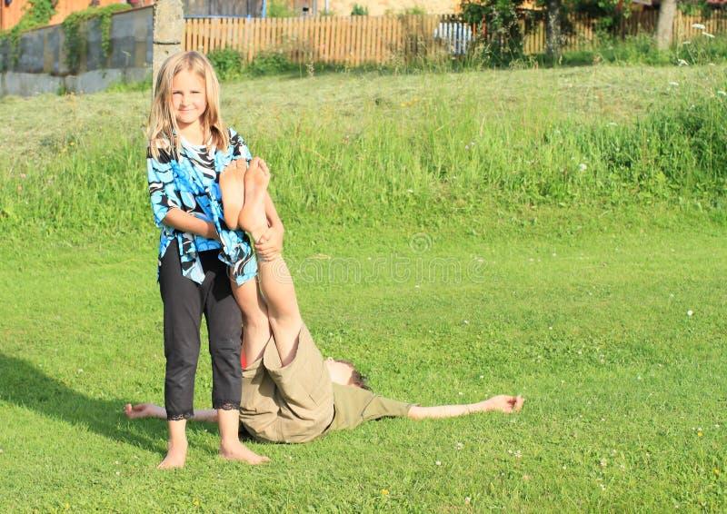 握男孩的脚的女孩 免版税库存照片