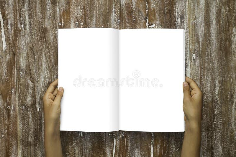 握男性手的特写镜头空白开放书白皮书板料 大模型自然木表背景 倒空假装  库存照片