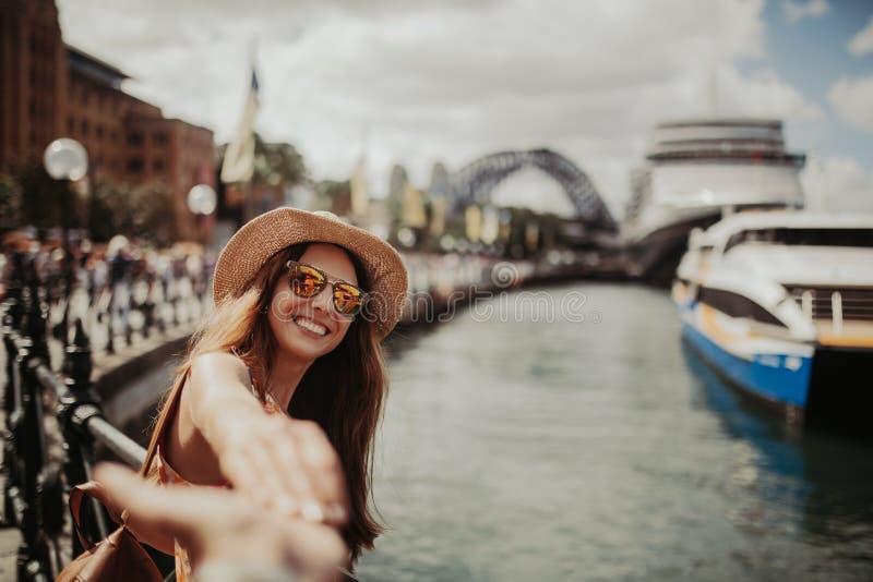 握男朋友手的太阳镜的妇女,当拍照片她,在悉尼港口时 免版税图库摄影