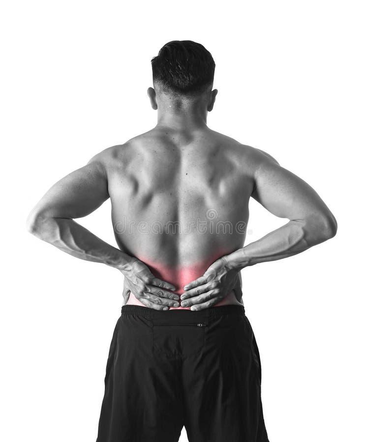 握疼痛低后腰部的年轻强健的身体体育人遭受在运动员重音的痛苦 库存照片