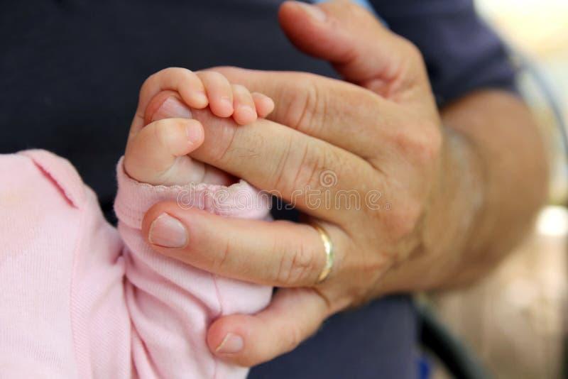 握祖父的手的新出生的女婴 库存图片